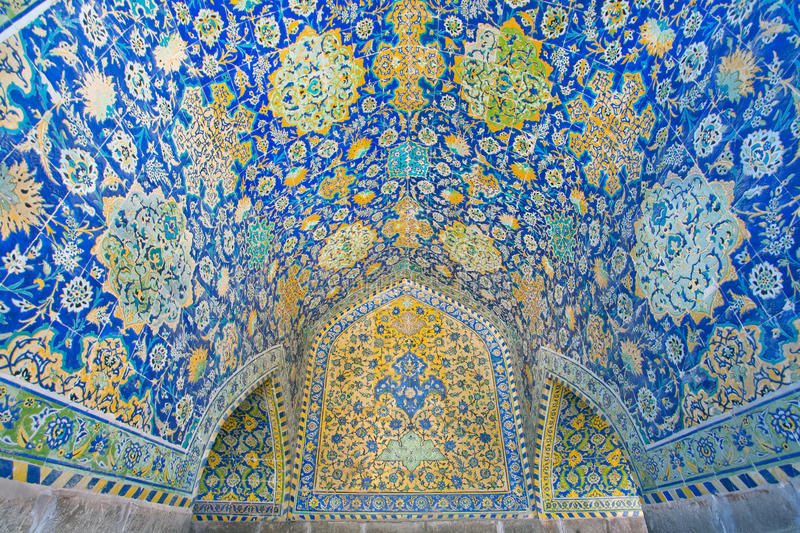 Persian tiles with floral patterns in the niche with wooden window of a historic building. Beautiful ceramic tile with Persian patterns in the niche with wooden stock images