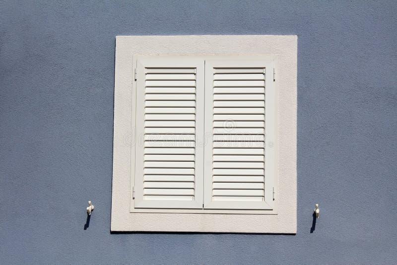 Persianas de ventana cerradas a estrenar con las bisagras y los tenedores del metal montados en la pared de la casa con la nueva  fotografía de archivo libre de regalías