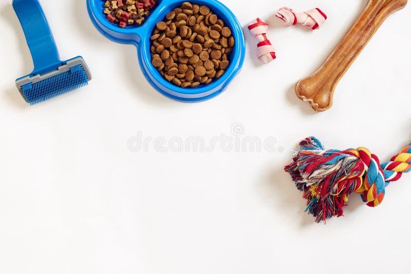Persiga os artigos do cuidado, isolados no fundo branco Alimentos para animais de estimação secos na bacia, no brinquedo e nos os fotos de stock royalty free