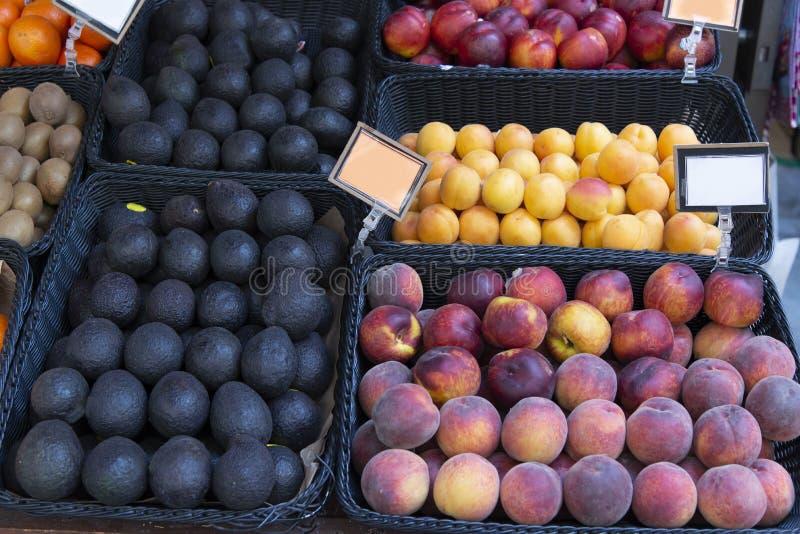 Persika och avokado på marknadshylla arkivbild