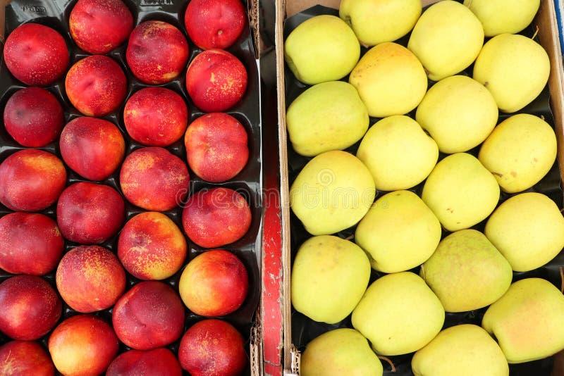 Persika och gulingäpple i korgen som säljer marknaden royaltyfri foto
