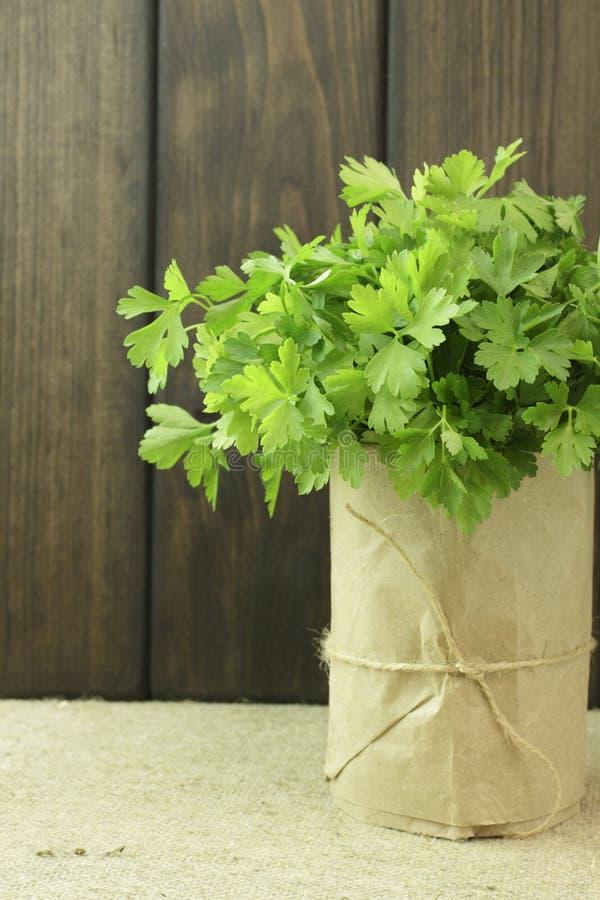 Persil vert dans un verre de papier sur une texture en bois images stock
