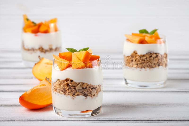 Persimmon śmietankowa błahostka w pięknych szkłach, świezi dojrzali owoc plasterki na białym drewnianym tle zdrowe jedzenie weget obraz royalty free