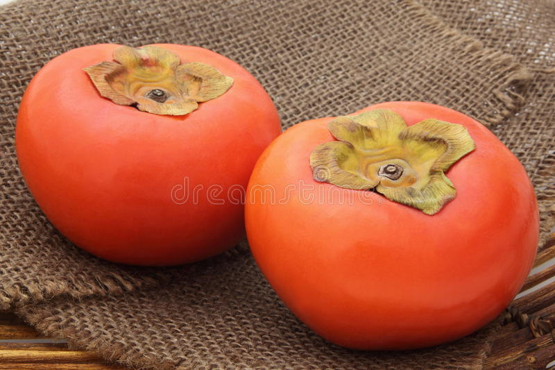 Persimmon on colander stock images