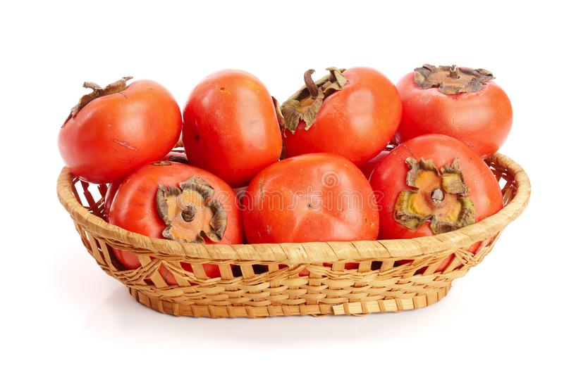 Persimmon fruit in a wicker basket isolated on white background close-up royalty free stock photography