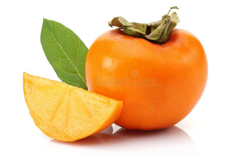Persimmon owoc z plasterkiem i liść odizolowywający obraz stock