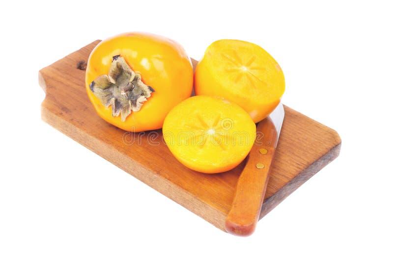 Persimmon owocowy cały, pokrojony na tnącej desce odizolowywającej na białym tle i obraz stock