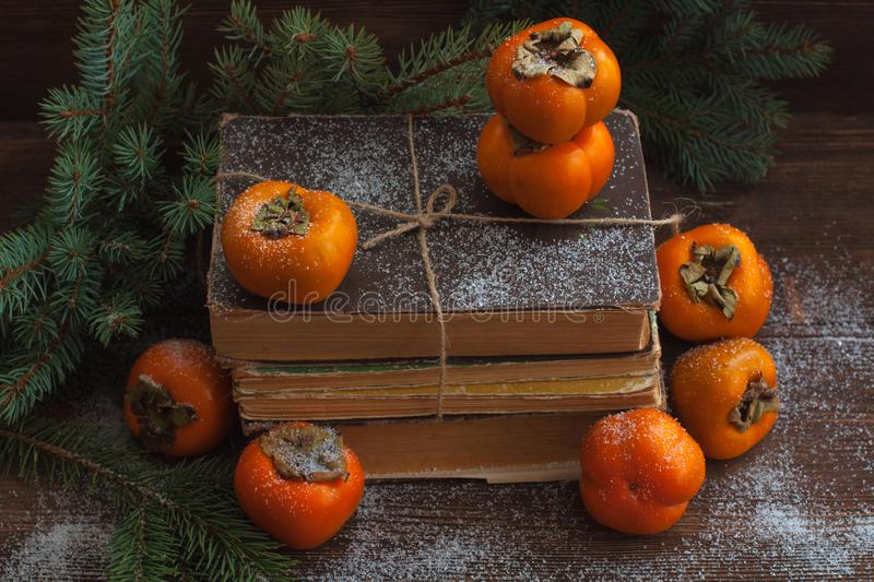 Persimmon on the pack of old books on the wooden background with branches of fir tree. Persimmon on the pack of old books on the wooden background. Toned stock photos