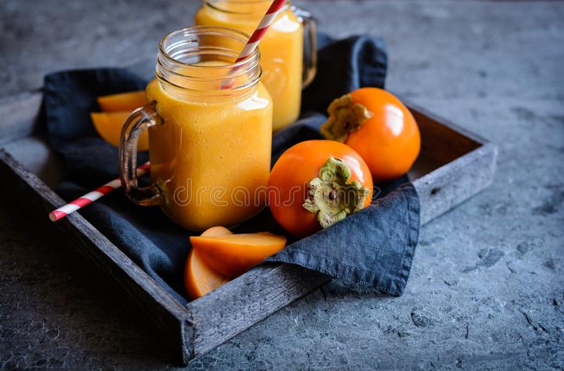 Persimmon smoothie in glass jars. Healthy Persimmon smoothie in glass jars stock images