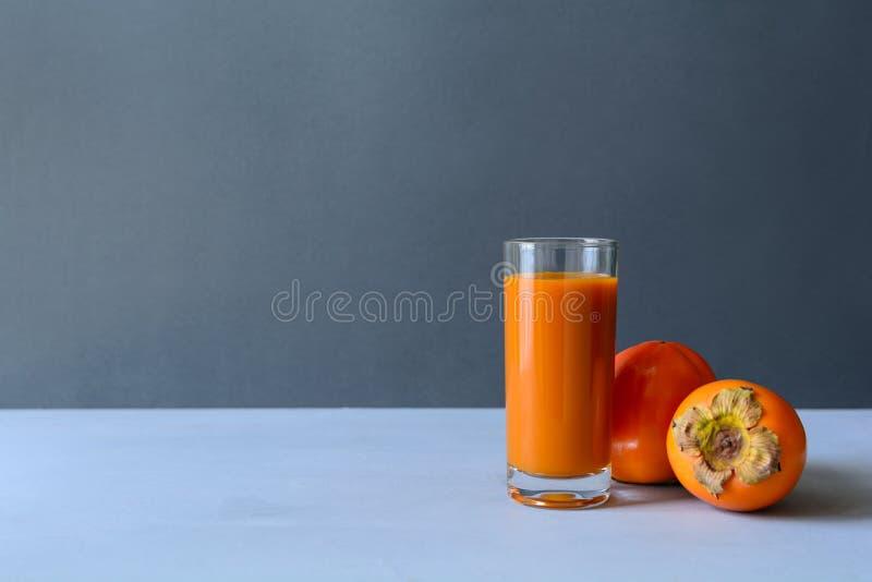 Persimmon sok z persimmons na szarym drewnianym tle jeść zdrowo pojęcia obraz stock