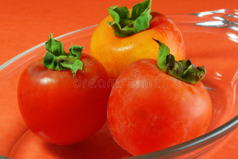 Persimmons at angle stock images