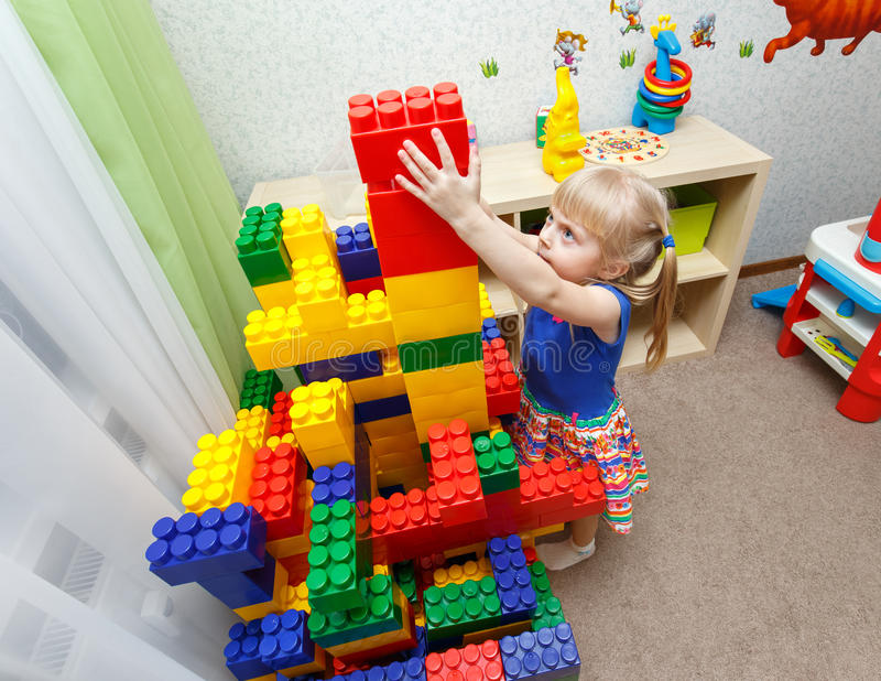 Persistent little girl building big block tower in daycare stock images