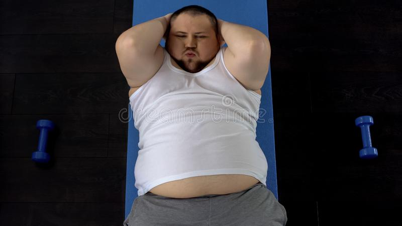 Persistent overweight man doing sit-ups lying on floor, genetic predisposition stock photography