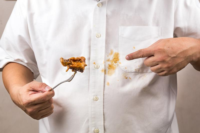 Person accidently spilled curry stain onto white shirt. stock photography