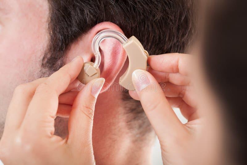 Person Adjusting Hearing Aid imagen de archivo libre de regalías