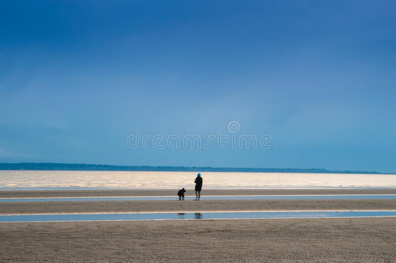 This person alone on the beach seems to enjoy social distancing royalty free stock images