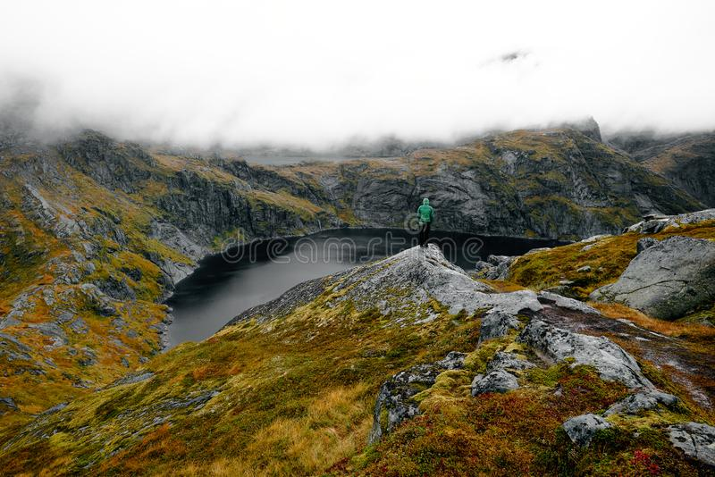 Person on alpine lake, Munken Mountain trail, Lofoten Islands, Norway. Person standing on edge of alpine lake on Munken Mountain trail near Sorvagen, Moskenesoy stock photo