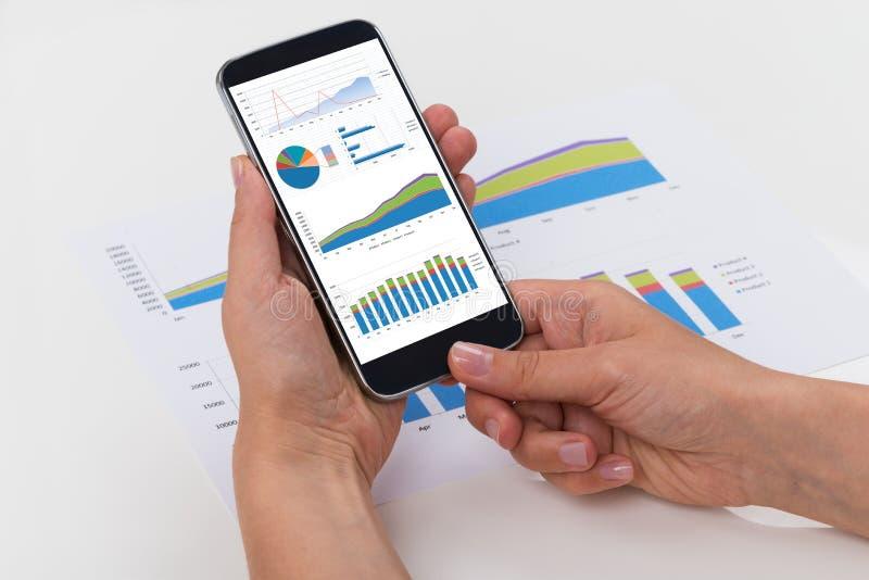 Person Analyzing Graphs On Mobile-Telefoon royalty-vrije stock afbeeldingen