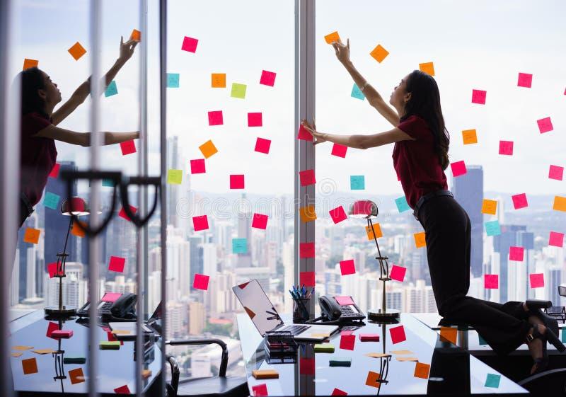 Person Attaching Many Sticky Notes ocupado na grande janela fotografia de stock