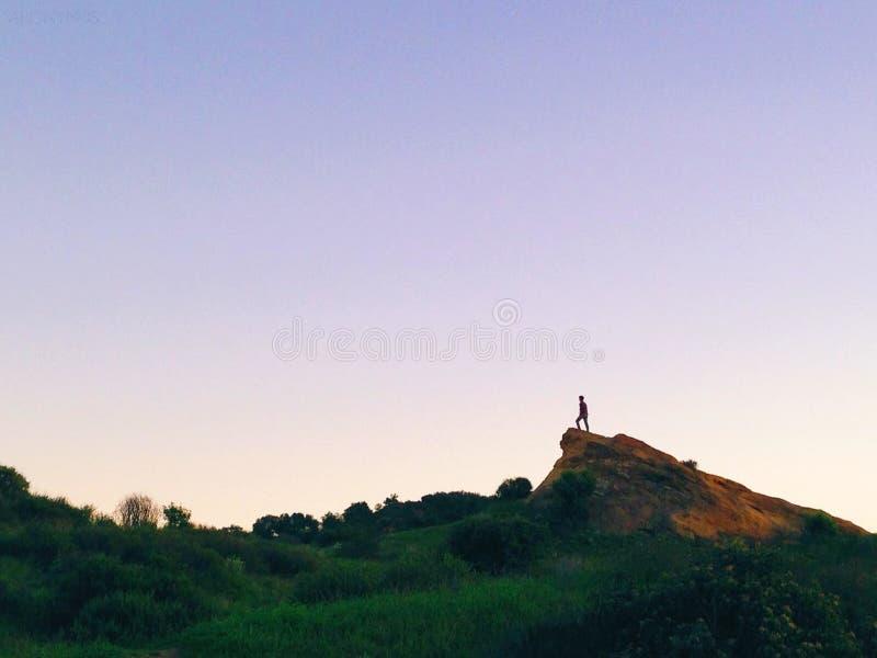 Person auf braunen Felsen in der Nähe von grünem Gras unter blauem Himmel unter Tage stockfoto