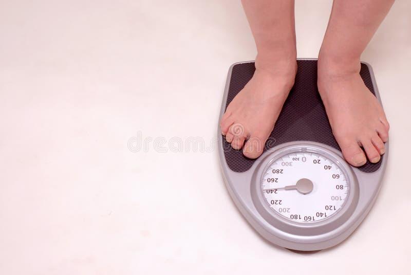 Person auf Gewichtskala stockbild