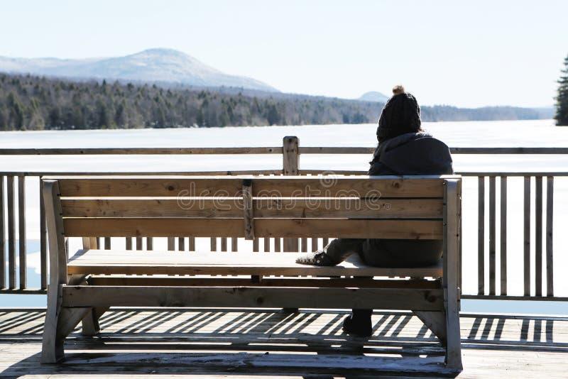 Person auf grauem Jacket auf der Braun-Holzbank Tagesbild stockbilder