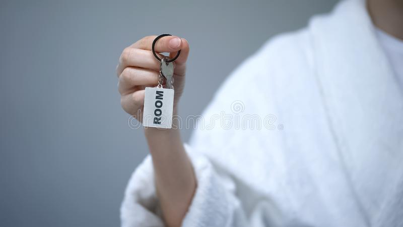 Person in bathrobe holding keys with Room word, health resort sanatorium, spa. Stock photo stock images