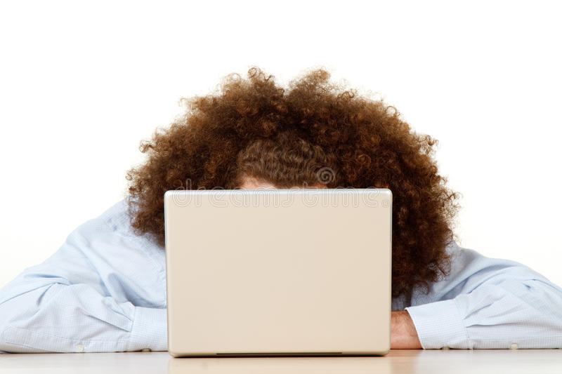 Person behind open laptop. Long frizzy or afro style hair of person working on open laptop computer; white studio background royalty free stock photo