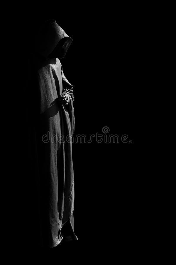 Person in black cloak. A figure covered in a cloak in a black background royalty free stock images
