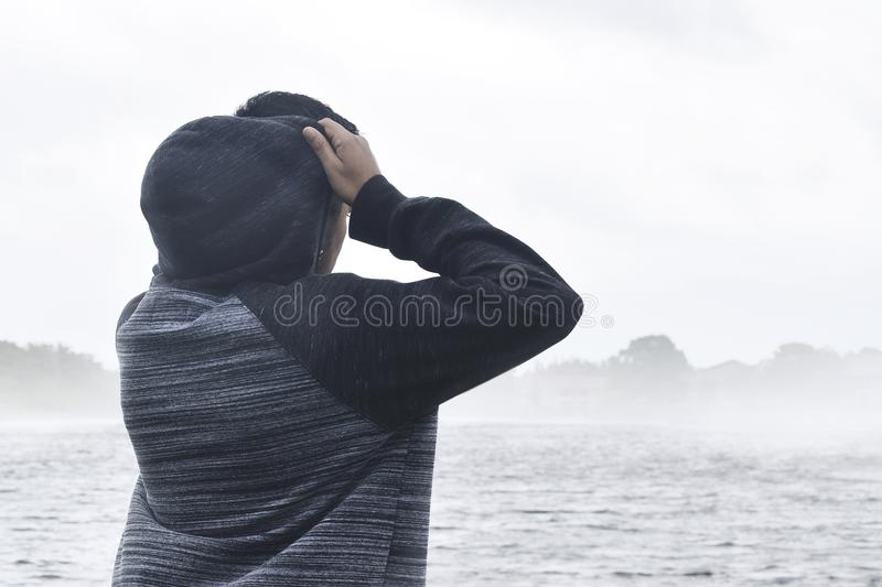 Person in Black and Grey Raglan Hoodie Near Body of Water royalty free stock photography