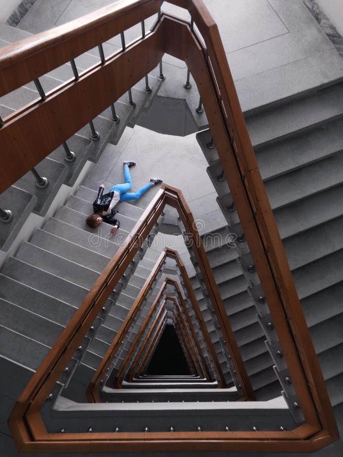 Person In Black Jacket And Blue Denim Pants Laying On Spiral Staircase stock photography
