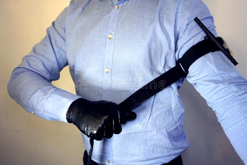 Person in black medical gloves Applies the tourniquet to his hand to prevent bleeding during the first aid. Trauma patient. Combat stock image