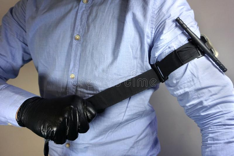 Person in black medical gloves Applies the tourniquet to his hand to prevent bleeding during the first aid. Trauma patient. Combat. Tactical Equipment. Combat royalty free stock image