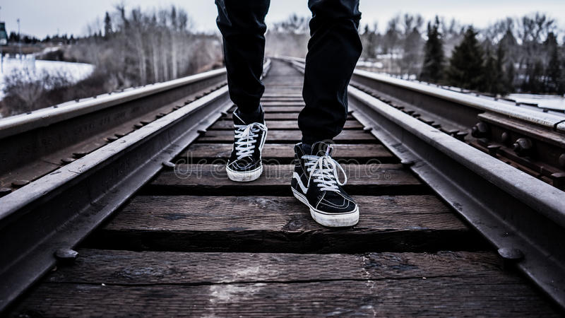 Person In Black Pants With Black Vans High Top Sneakers Standing On Railroad Tracks During Daytime Free Public Domain Cc0 Image