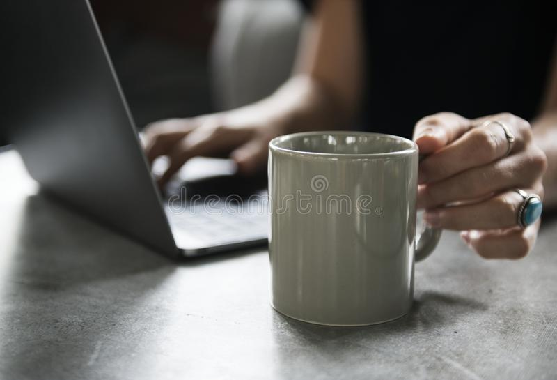 Person in Black Top Holding White Ceramic Mug and Using Laptop Computer royalty free stock image