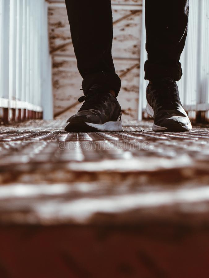 Person in Black-and-white Shoes Standing on Brown Metal Floor royalty free stock photos
