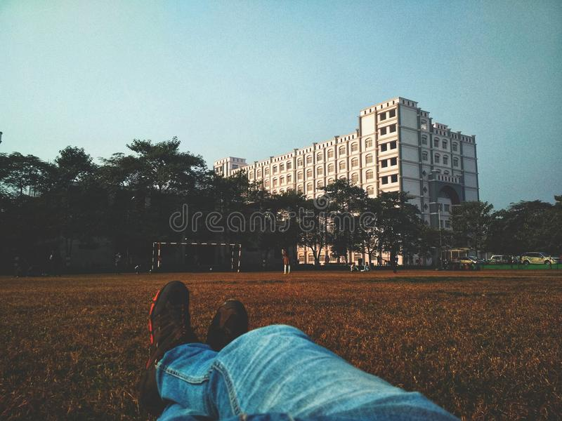 Person in Blue Denim Jean Lying on Brown Grass Field Looking at White Multi-storey Building royalty free stock photos