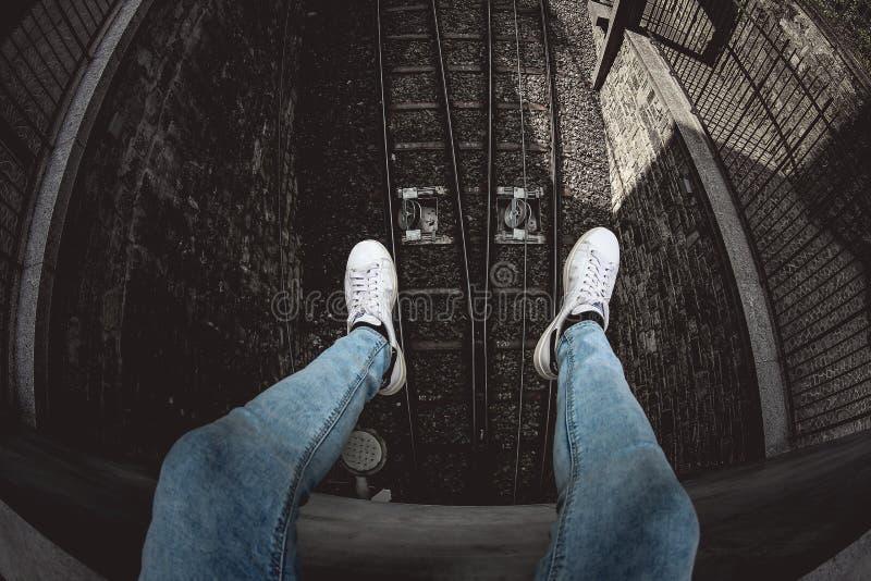 Person in Blue Denim Stonewusalkgetüschte Jeans und White Low-Top-Sneakers stockfotos
