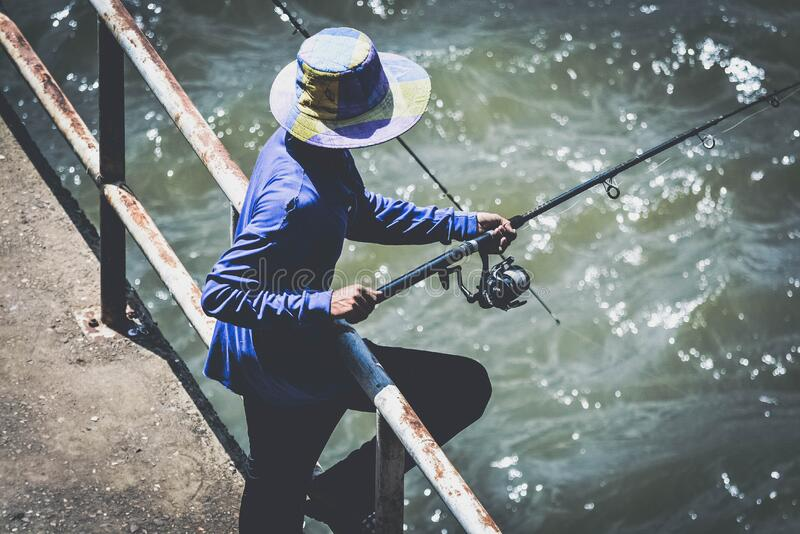 Person in Blue Long Sleeve Shirt and Black Pants Using Fishing Rod stock image