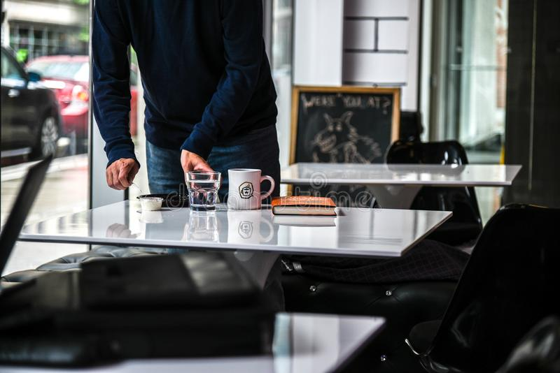 Person in Blue Long-sleeved Shirt Holding Clear Glass Cup royalty free stock photo
