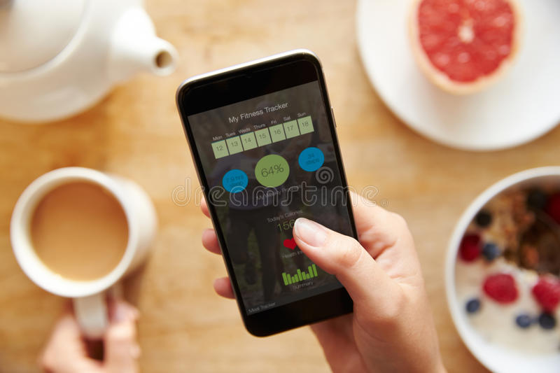 Person At Breakfast Looking At Fitness App On Mobile Phone royalty free stock photo