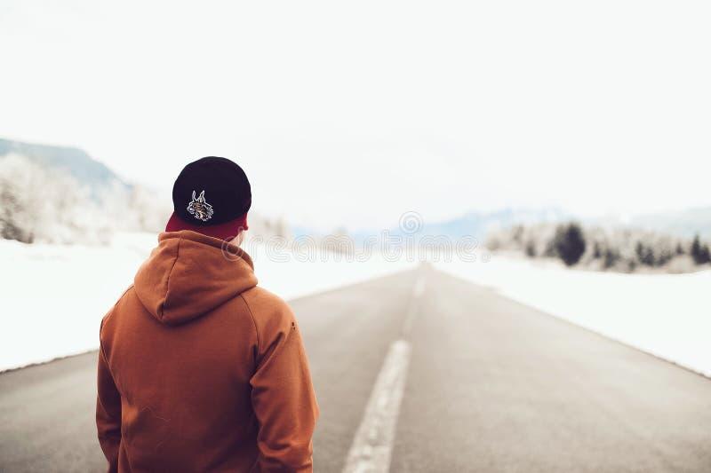 Person in Brown Hoodie stehend auf Asphalt Road lizenzfreies stockbild