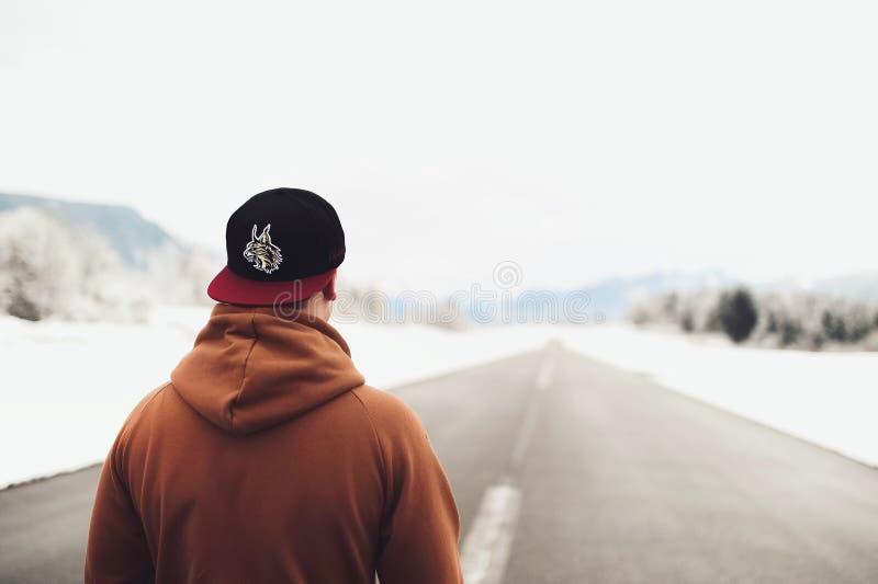 Person in Brown-Hoodie und in gepaßter Kappe gehend auf Straße stockfotos
