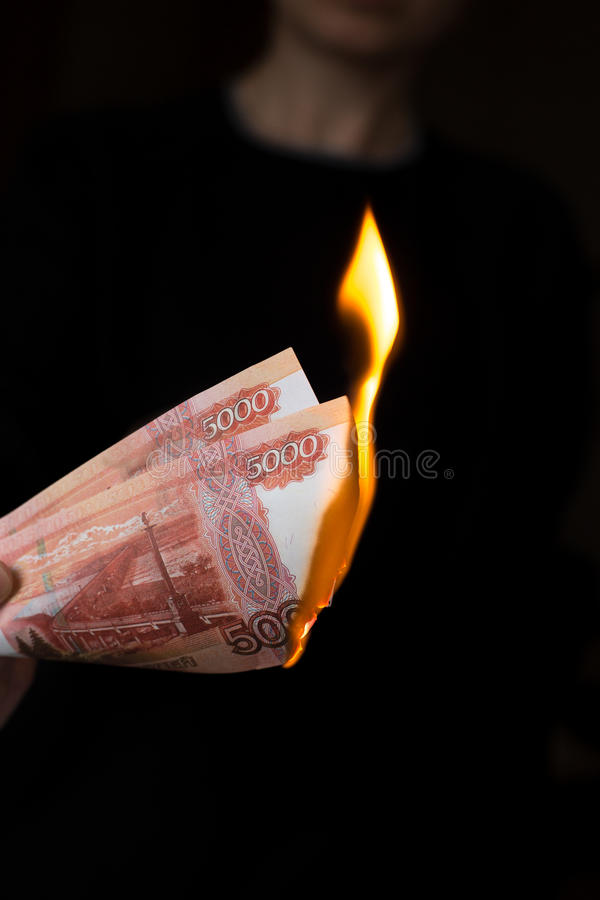 Person burns rubles. Person burns two of five thousand Russian banknotes royalty free stock photos
