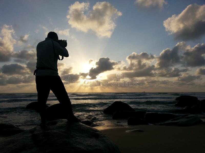 Person Capturing Photo Near Sea Under Clear Blue and White Cloudy Sky during Daytime royalty free stock image