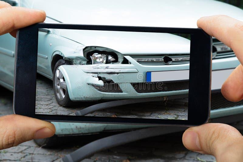 Person Capturing The Picture Of bruten bil arkivfoton