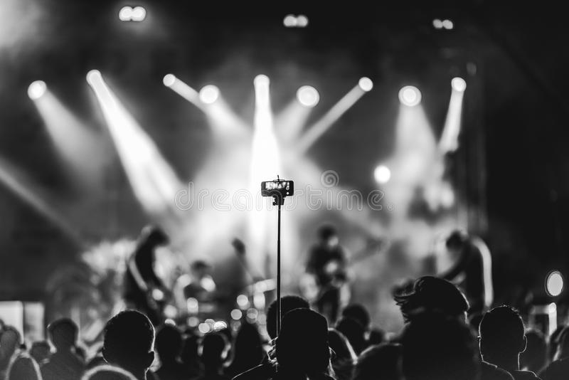 Person capturing a video. On a mobile phone with selfie stick at a music festival royalty free stock images