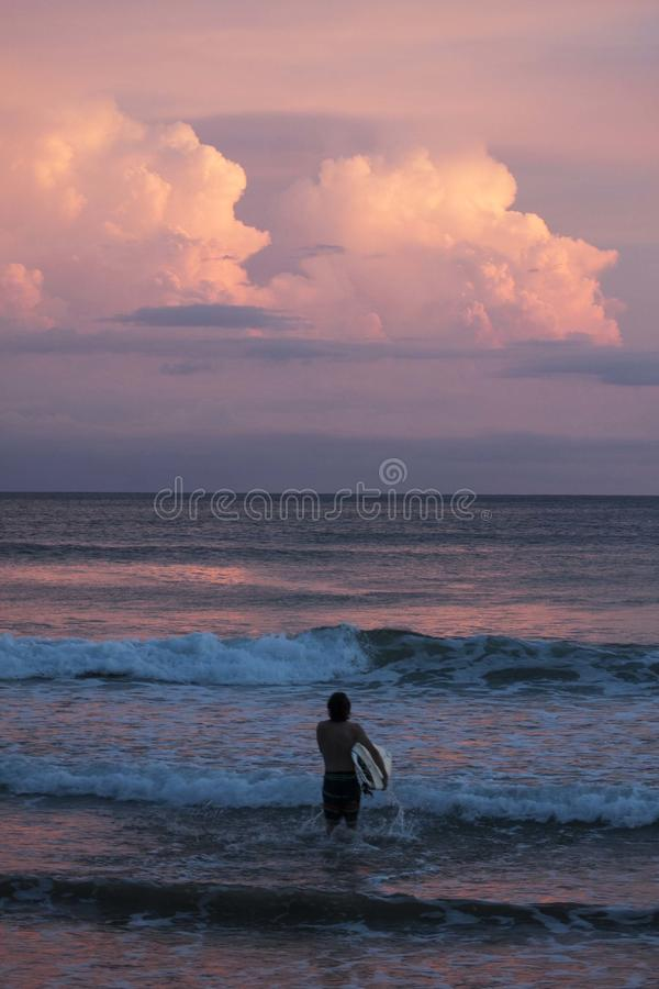 Person Carrying Surfboard Walking Against Sea Waves during Golden Hour stock images