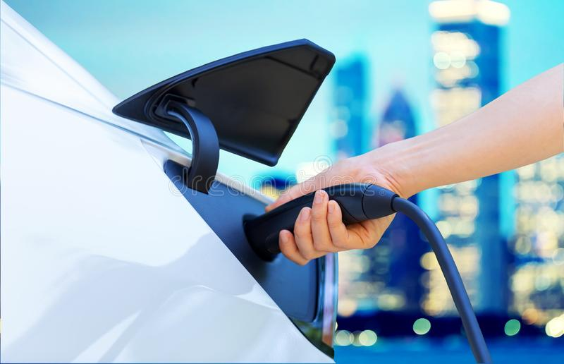Person charging an electric vehicle royalty free stock images