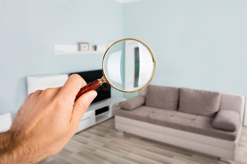 Person Checking Living Room Using förstoringsglas royaltyfri bild